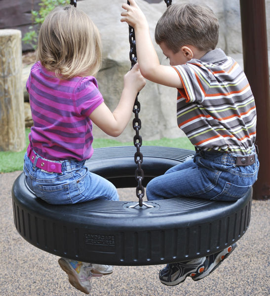 Kids wearing Dapper Snappers toddler belts while on a tire swing